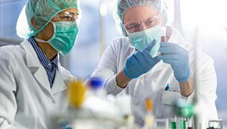 Researchers wearing personal protective equipment look at a vial